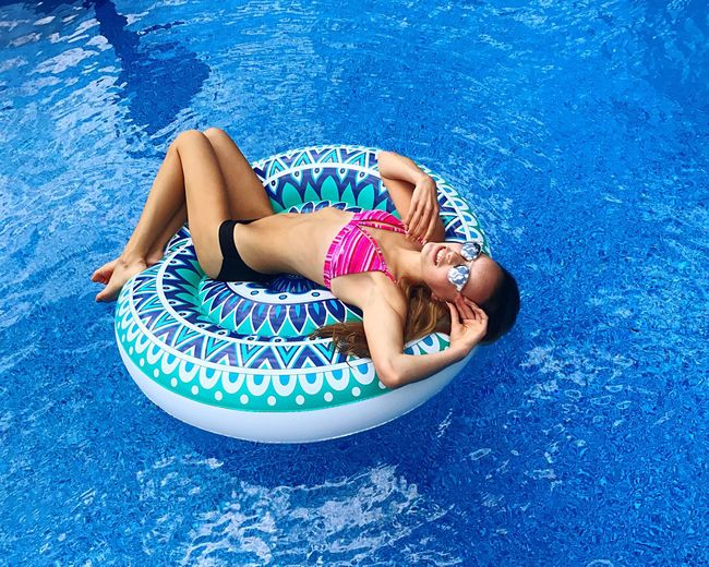 High Angle View Of Woman Wearing Sunglasses While Relaxing On Inflatable Ring At Swimming Pool