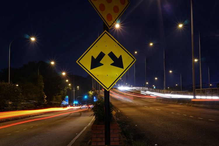 Close-up of arrow symbols on road at night