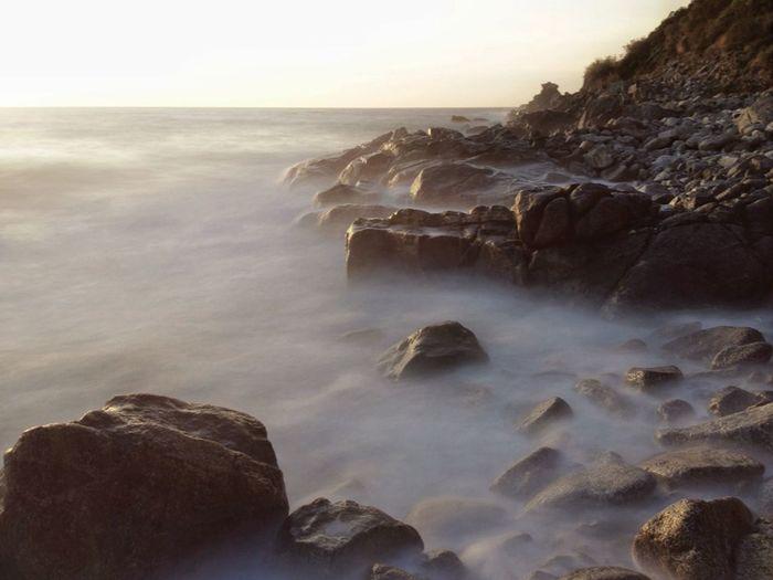 Rocks over sea against clear sky