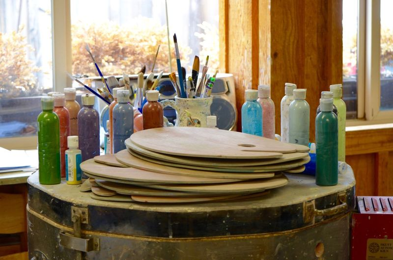 Colorful paint bottles with palette on drum at workshop
