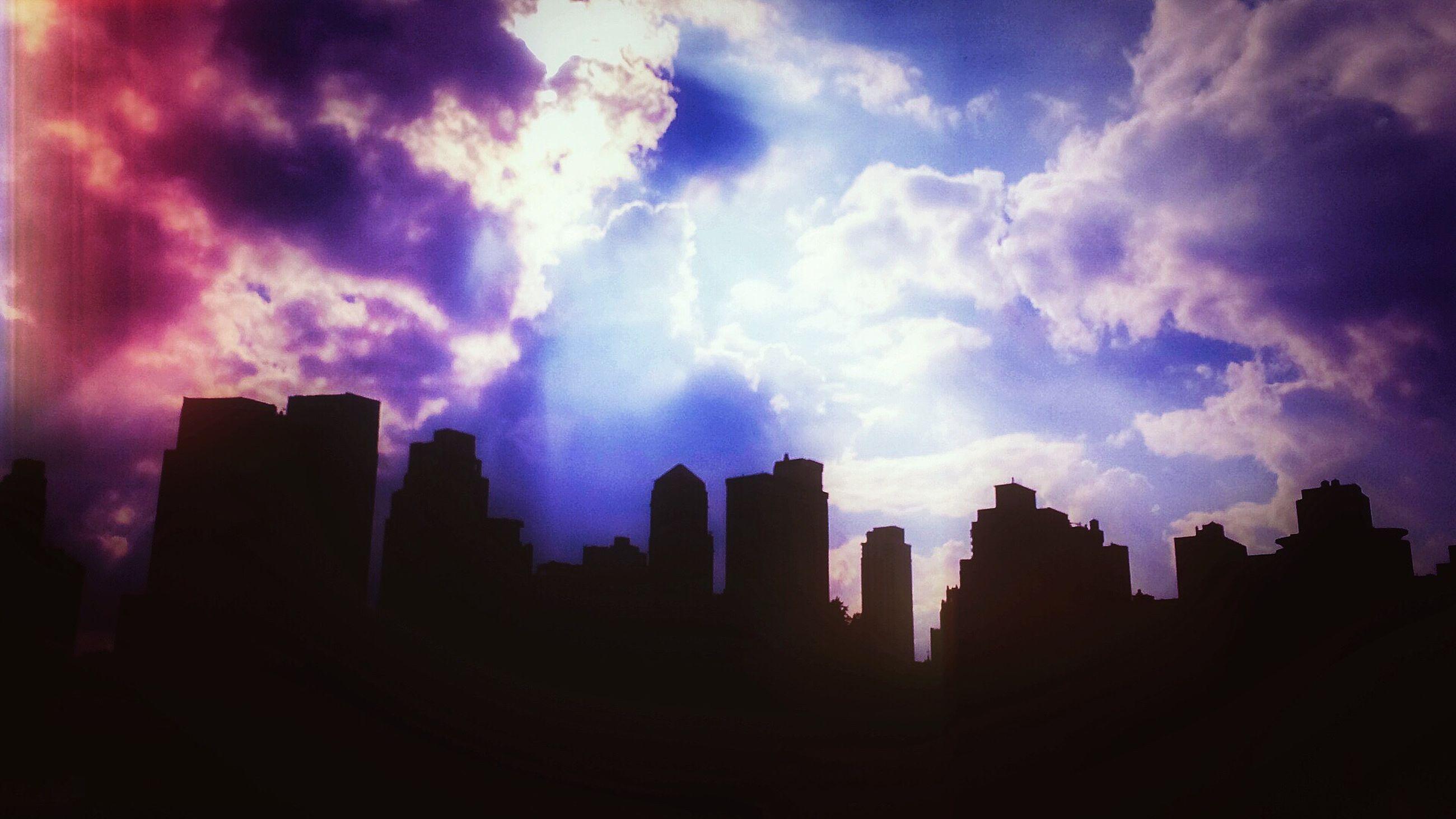 building exterior, architecture, sky, built structure, city, cloud - sky, silhouette, skyscraper, cityscape, cloudy, sunset, cloud, urban skyline, sunbeam, outdoors, travel destinations, building, dark, weather, dusk