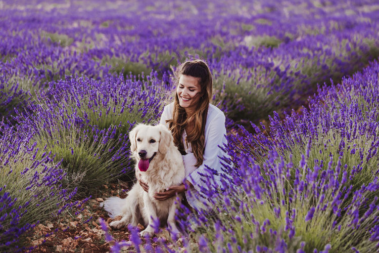 Woman with dog by purple flowering plants on land