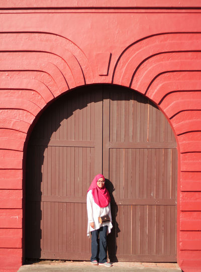 Portrait of woman wearing hijab standing against closed door