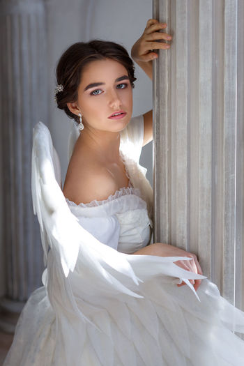 Portrait of a beautiful young woman in a white dress and angel wings, standing with a pleading look