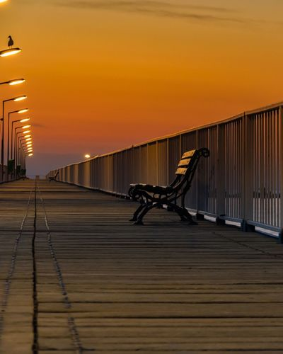 Empty bench on bridge against sky during sunset