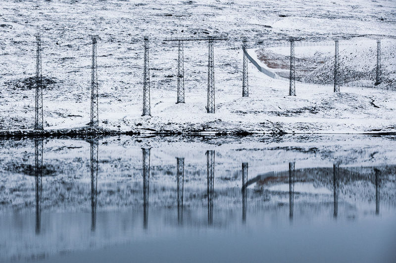 Power lines reflecting in Winter lake in Faroe Islands No People Snow Water Winter Nature Cold Temperature Day Tranquility Beauty In Nature Scenics - Nature Reflection Lake Outdoors Non-urban Scene Tranquil Scene Frozen