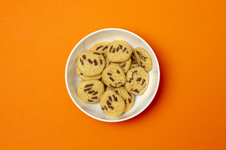 High angle view of cookies in bowl against orange background