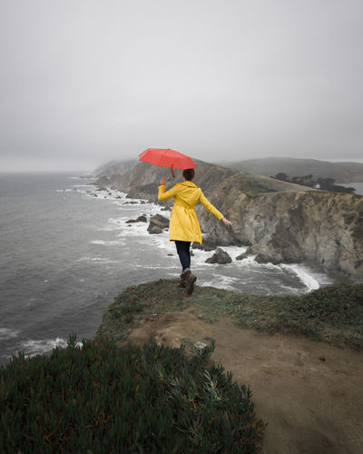 Rear View Of Woman With Umbrella Standing By Sea On Cliff