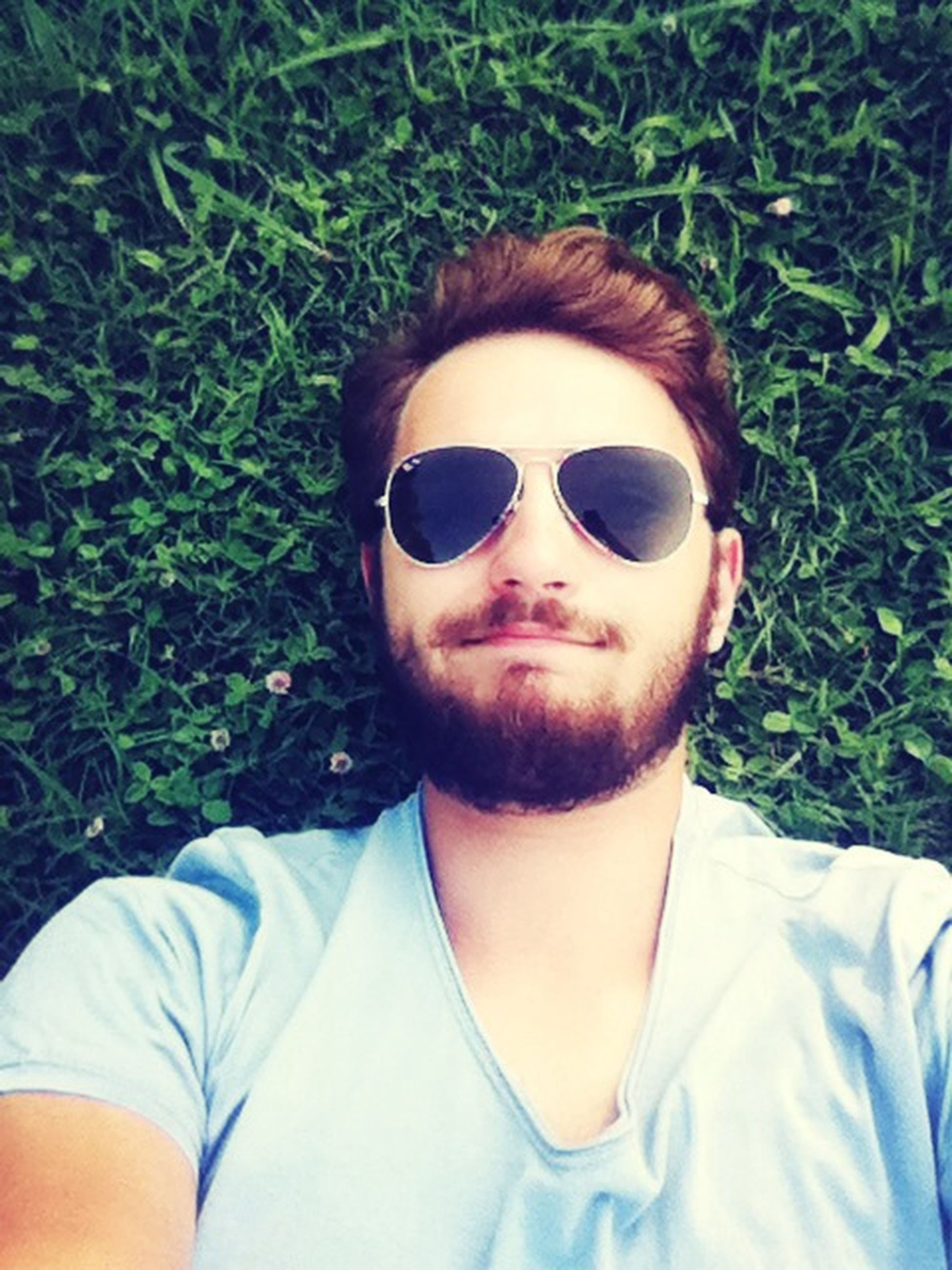 looking at camera, portrait, lifestyles, person, front view, young adult, grass, leisure activity, sunglasses, headshot, casual clothing, smiling, green color, young men, high angle view, field, relaxation, day