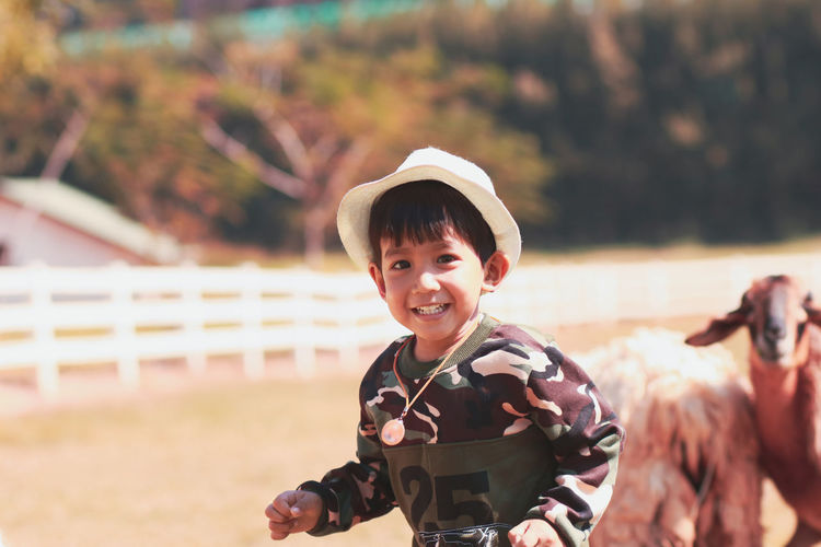 Portrait of smiling boy wearing hat standing outdoors at farm