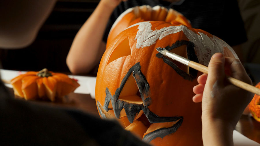 Young boy carving and painting a pumpkin for Halloween on a table Celebration Getting Ready For Halloween Halloween Ready Young Boy Brush Carving - Craft Activity Food Harvest Holding Indoors  One Person Painting Preparation  Pumpkin