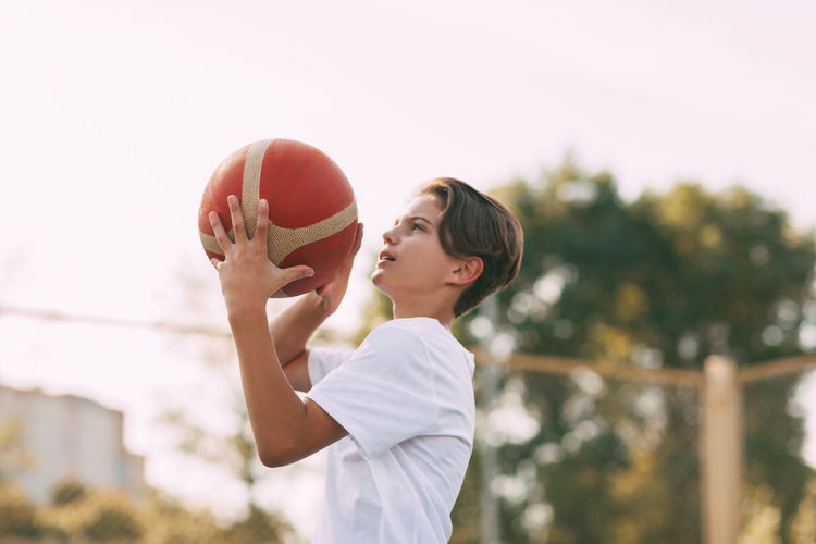 Side view of boy playing with basketball against clear sky