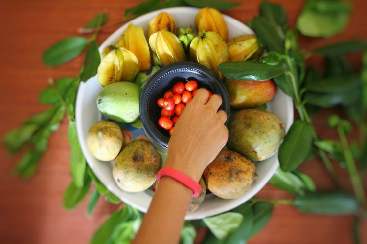 Grabbing for cherries Human Hand Healthy Eating Basket Food And Drink Freshness Fruit Food Close-up Day Cherries Star Fruit  Mango Tropical Summer Bright Colorful Healthy Lifestyle Leaf Indoors  Hand Top View Reaching