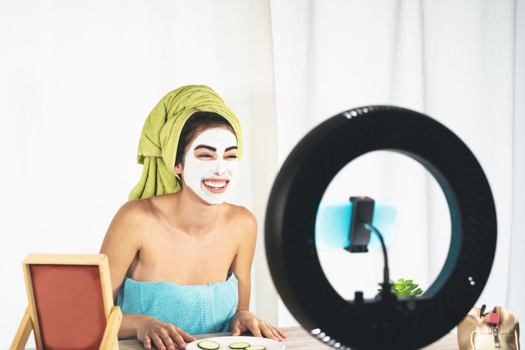 Smiling young woman with facial mask filming over smart phone