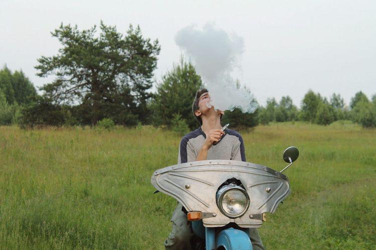Man smoking hookah while sitting on motorcycle at field