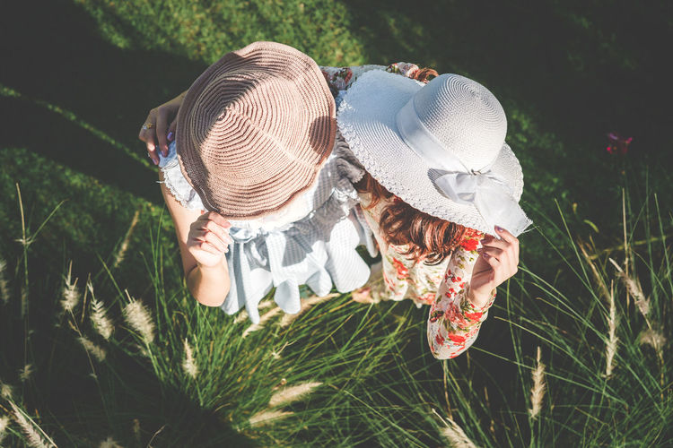 High angle view of couple younger women catching her hat and standing on field. Nature Outdoors Vacations Travel Tourism Travelling English Garden Woman Portrait Together Couple Friendship Friends Enjoying Life Relaxing Leisure Lifestyles Fun Pampas Grass Hat Touching Sky Top View Field Feelings