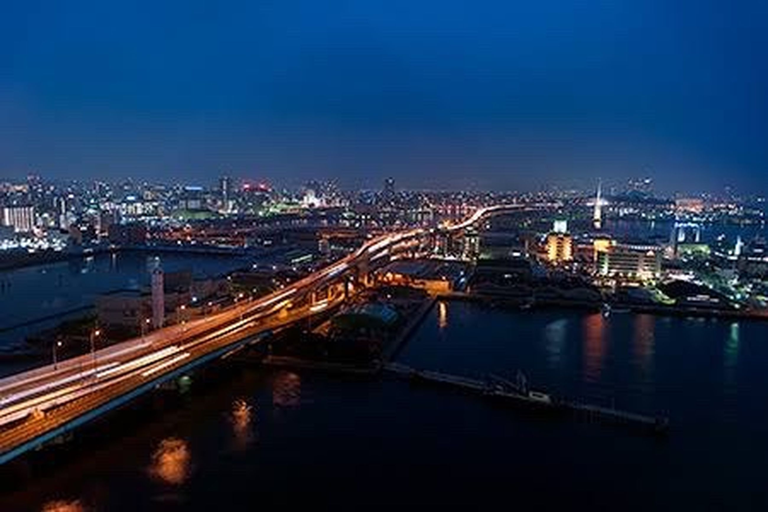 architecture, illuminated, built structure, building exterior, city, connection, night, transportation, bridge - man made structure, river, cityscape, high angle view, clear sky, water, copy space, bridge, blue, sky, engineering, city life
