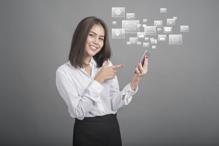 Adult Beautiful Woman Business Business Businesswoman Chats Communication Connection Cyberspace Finance Futuristic Global Communications Globalization Indoors  Internet One Person One Woman Only Smart Phone Smiling Studio Shot Talking Photo Tech Technology Touch Screen Young Adult