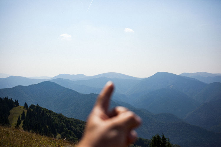 Cropped hand of person pointing at mountain range against sky