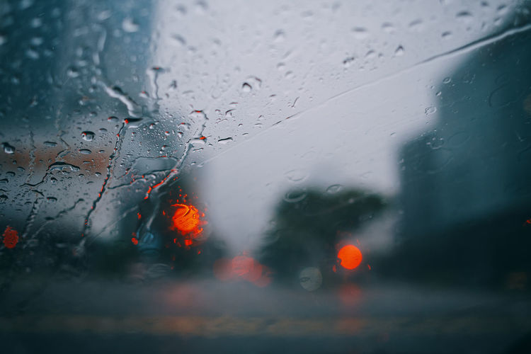 Raindrops on glass window of car with defocused traffic lights in background