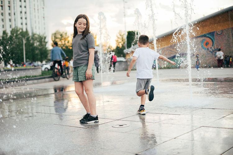 Full length of children on wet umbrella during rainy season