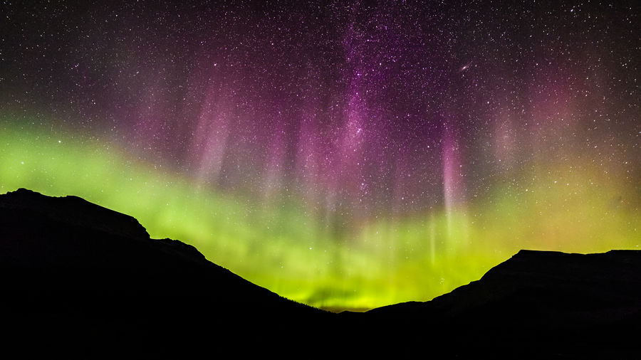 This is a shot from 2017 of the Aurora Borealis or Northern Lights in Mt Robson Provincial Park. This was the night I took my shots of STEVE to the south over Berg Lake and Mt Robson from the same position (this shot looks north). The red/pink band of forms at around 250 – 500 km altitude from high energy state excited oxygen atoms emitting light at 630 nm. The bottom layer is the more typically seen green aurora that forms between 100 – 250 km altitude by excited oxygen atoms emitting light at 557.7 nano-metres. Night Scenics - Nature Space Star - Space Sky Astronomy Tranquil Scene Tranquility No People Silhouette Idyllic Nature Mountain Green Color Non-urban Scene Majestic Illuminated Outdoors Aurora Polaris Purple Power In Nature Aurora Borealis Northern Lights Skyline British Columbia, Canada