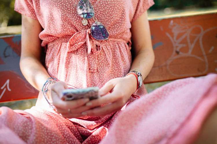 Midsection of young woman using phone while sitting on bench