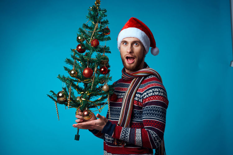 Full length of man with christmas tree against blue background