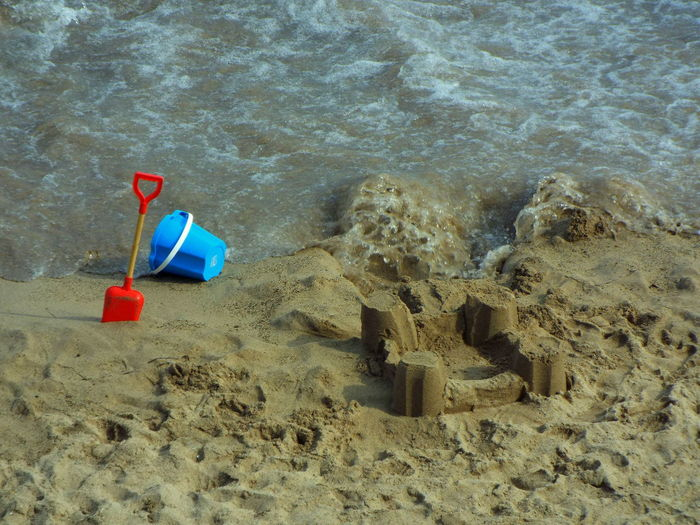 High angle view of sand castle with bucket and spade at beach