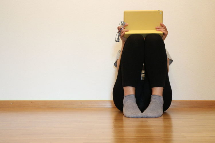 Woman using laptop while sitting on floor against wall