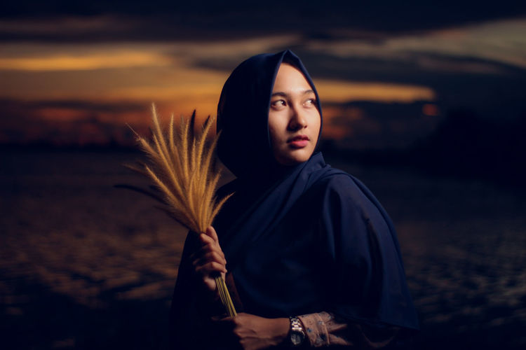 Woman looking away while holding reed against sky during sunset