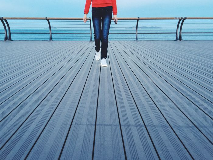 Low section of woman walking on pier