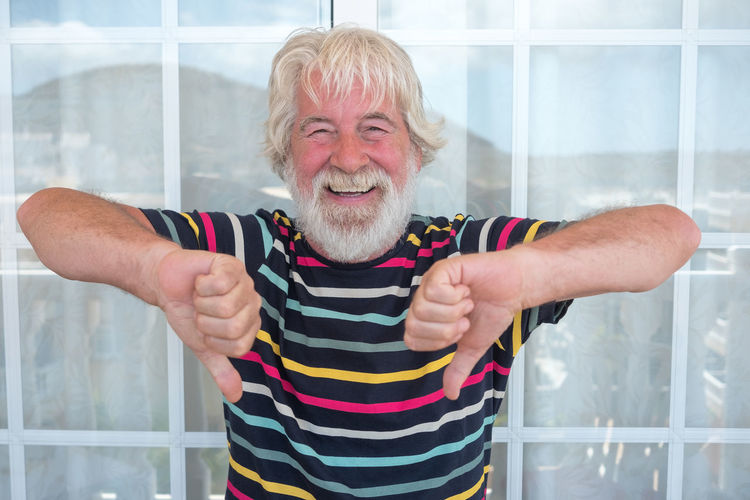 Portrait of senior man showing thumbs down against window