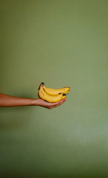 Midsection of woman holding fruit against wall