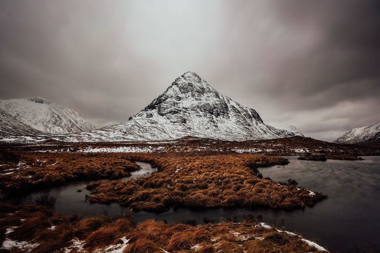 Mountains in scotland in rannoch moor with dark cloudy sky and lake