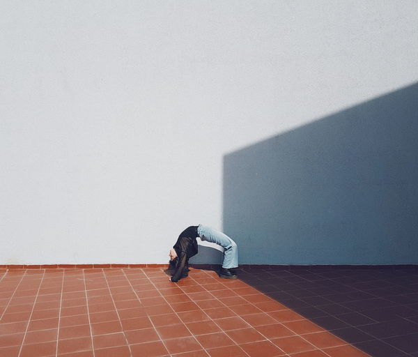 Full length of man relaxing on floor against wall