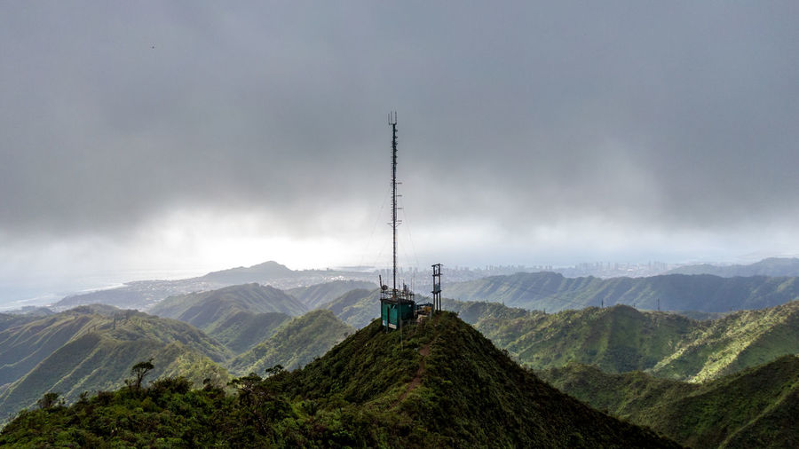 Stunning aerial drone view of a communications tower at the summit end of famous Wiliwilinui Ridge Hiking Trail near Honolulu on the island of Oahu, Hawaii. Coastline in the background & cloud cover. Hiking Trail Honolulu  Hawaii Oahu Mountain Mountain Ridge Summit Communication Communications Tower Radio Tranquility Trail Wiliwilinui Hiking Outdoors Outdoor Sport Cloud - Sky Cloud Cover Rainforest Scenics - Nature Beauty In Nature Environment Mountain Range Travel Mountain Peak