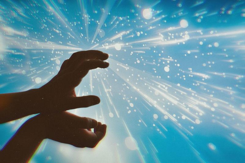 Cropped hands gesturing against sky