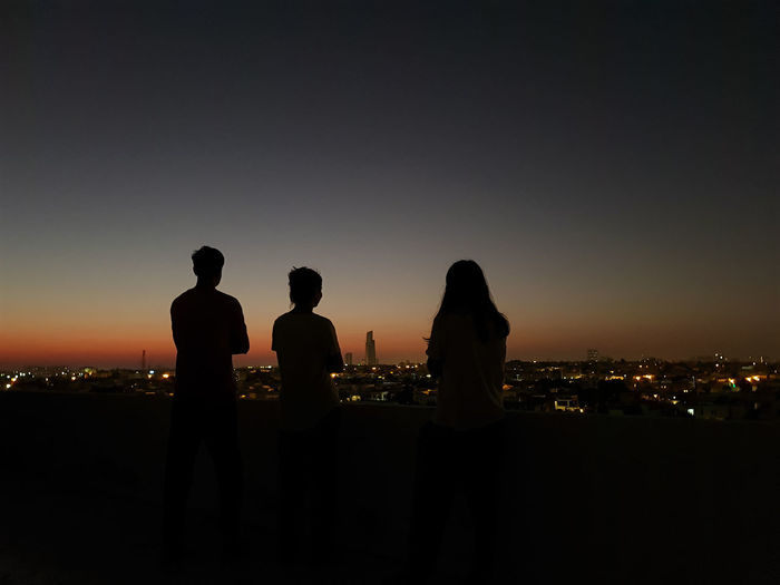 Silhouette people looking at cityscape against sky during sunset