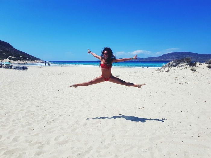 Full Length Of Woman Jumping At Beach Against Blue Sky