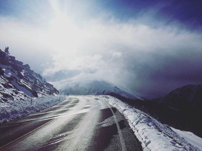 Empty Road By Mountain Against Sky During Winter