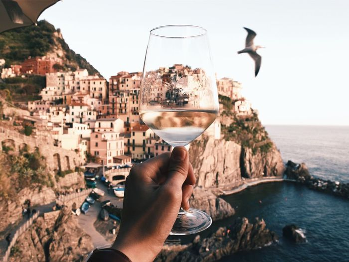 Cropped Hand Holding Wineglass Against Buildings