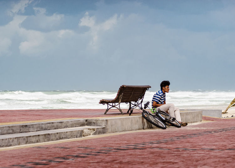 Young man with bicycle sitting on promenade against sky