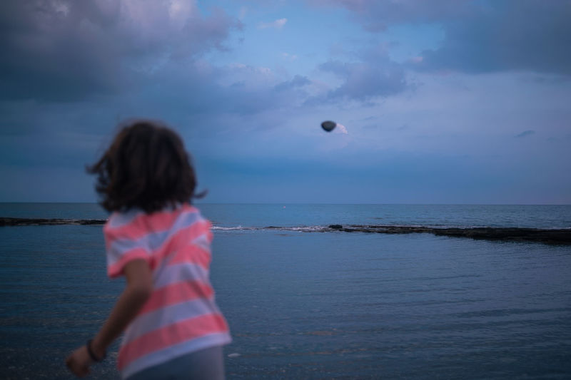 Rear View Of Girl Throwing Stone Towards Sea Against Cloudy Sky
