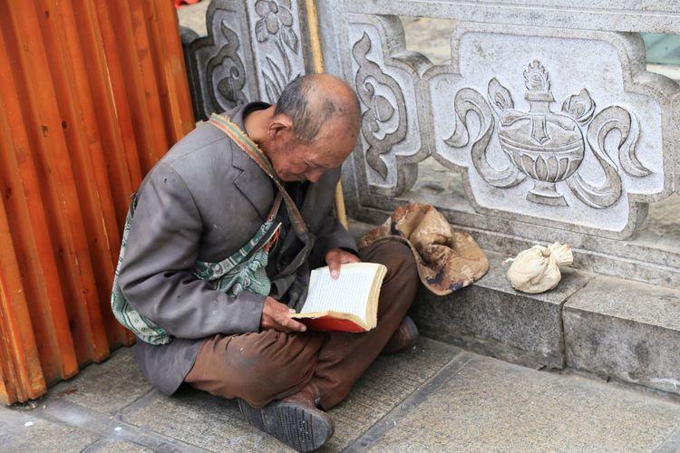 Full Length Of Man Reading Book On Ground