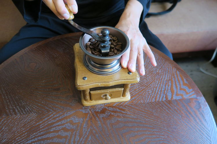 High angle view of person grinding coffee on table