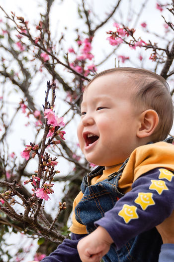 Close-Up Of Baby Boy Laughing Against Tree