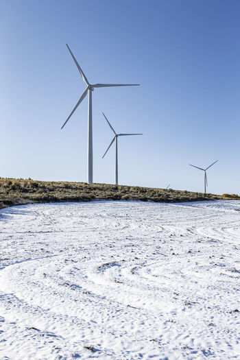 Wind turbines on field against clear sky during winter