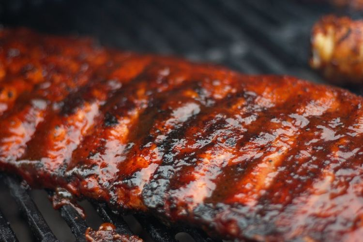 Cropped image of grilled meat on metal grate