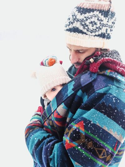 father and baby in winter while snowfall Baby Carriage Baby Care Father Snowfall Snowstorm Warm Clothing Active Lifestyle  Hike Dad Winter Warm Clothing Clothing Cold Temperature Hat Knit Hat Males  Glove Snow Portrait Young Adult Childhood
